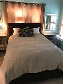 full sized bed with bedding and headboard