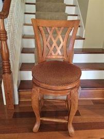 One of three oak bar stools.