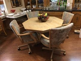 Breakfast nook table with 4 matching chairs with rollers.
