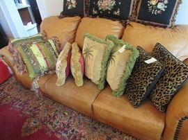 Decorator pillows on thick leather couch/sofa with large nailhead trim