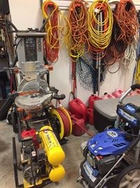 garage filled with tools and generators, portable heater, life jackets, air compressor, tons of tools, craftsman tool chests, nail guns, gas cans, and much more.