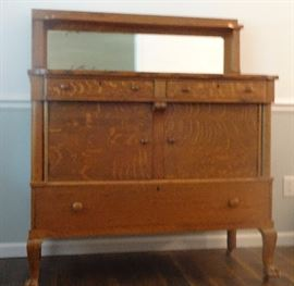 antique quarter sawn oak sideboard with beveled glass mirror and shelf , empire style, claw foot on wheels made by West End Furniture Co Rockford, Il.