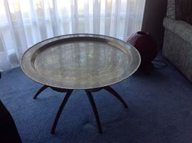 Brass table with spider legs from the 1960's.   There is a red decorative light sitting to the right of the table.  Both items were brought from Japan.