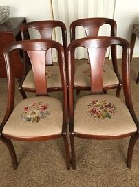 A set of mahogany mid-century chairs with needlepoint seats