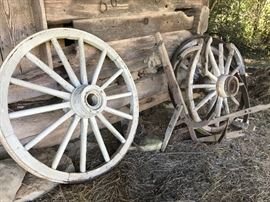 Heavy old wagon wheel and parts of wheels