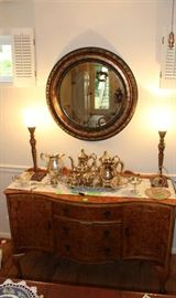 The beautiful round mirror over the buffet.