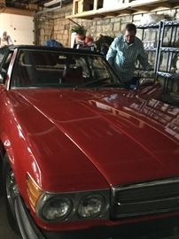 1978 Mercedes 450 SL. Red. Black convertible top. Red and black interior. Seriously cute car