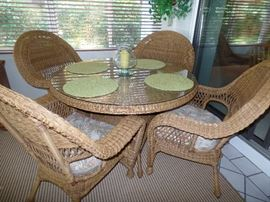 Like new wicker, round  glass top table and 4  arm chairs