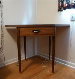 Mid Century Modern corner table, pencil legs, one drawer, glass top.