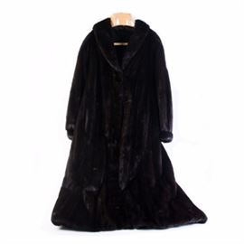 """Full-Length Black Mink Fur Coat: A full-length black mink fur coat. The coat features a shawl style collar with cuff sleeve and flared silhouette. The coat has two exterior pockets and a interior pocket with monogrammed initials """"SGK."""" The piece has no identifying tags."""