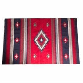"""Handwoven Mexican Wool Rug: A handwoven Mexican wool rug. The rug features cream, red, navy and gray striped sections with geometric diamond patterns throughout. The rug has natural warp fringe to both ends. The rug is marked with a tag reading """"The Zapotec Collection, 100% Wool, Handwoven in Teotitlan Del Valle, Oaxaca, Mexico"""" to the underside."""