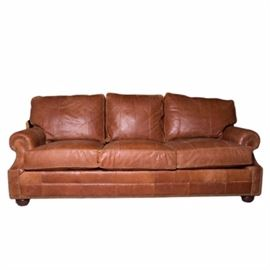 Lexington Furniture Cognac Leather Couch: A Lexington Furniture cognac leather couch. The couch features a distressed cognac leather upholstery with brass nail head trim. The couch has rolling arms and rests on four round walnut legs.