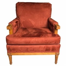 Suede Accent Chair: A suede accent chair. The arm chair features a burnt orange suede upholstery with oak stained arms and legs. The chair rests on fluted legs with craved foliate details at the corners.