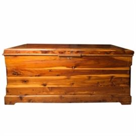 Vintage Cedar Chest: A vintage chest. The chest is made of cedar wood and has a shellac finish. The piece features a hinged lid that opens to reveal ample space for storage and a sliding drawer. The piece rests on bracket feet. No maker's mark is present to the piece.