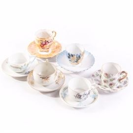 """Assorted Demitasse Teacups and Saucers: A set of six assorted Demitasse tea cups with saucers. The cups include one unmarked gold tone bamboo design, a pastel floral design marked Rosenthal Donatello, a pink floral design marked Victoria Ceramic, a blue and gold tone with yellow flowers marked """"20"""" to bottom, a red and gold tone cup marked """"13"""" to bottom, and a geometric floral design marked Eamag Bavaria."""