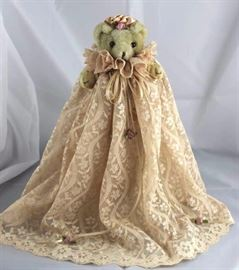 "Victoria-249. Victorian Creations. In Synthetic-It  beigh standing at 5.13"" H in excellent conditon.  Small bear on a stand in a champagne beige lace  christening dress with ribbons and fabric flowers.  Trimmed peach ribbon hat."