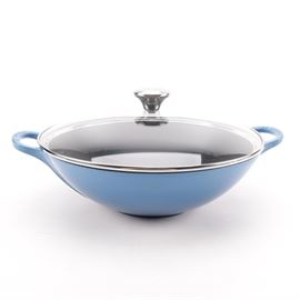 "Le Creuset Enamel Wok: A Le Creuset enamel wok. This piece is presented in a blue finish with side handles and a removable glass lid. The lid is adorned with a metal frame and round knob that is embossed, ""Le Creuset"". It is marked to the underside, ""Le Creuset, 32, France""."