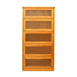 Contemporary Oak Barrister Bookcase: A contemporary oak barrister bookcase. This piece is fashioned after a vintage barrister bookcase. It offers five shelves with glass front doors that slide up and under the above shelf. The top door features a leaded glass style front, set in diamond patterns. The doors open with round white and brass knobs. It stands on a plinth base.