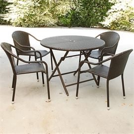 Woven Patio Table and Chairs: A woven patio table and chairs. This brown metal patio set feature a round woven top table with hole for umbrella, (not included) and an X shaped open metal base and comes with four matching round back woven chairs with curved arms, open sides round front seats and straight legs on peg feet.
