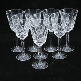 "Waterford Crystal ""Lismore"" Tall Water Goblets: A set of Waterford Crystal ""Lismore"" tall water goblets. This set features eight glasses with brilliant cross and leaf motif, tapered stem, and round bottom. A Waterford sticker and acid etched logo is seen at the base of each goblet."