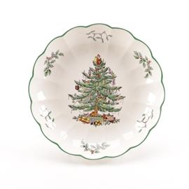 "Spode Christmas Themed Plate: A Christmas themed plate. The piece is composed of ceramic and round in shape with a green trim. The center of the plate features a large Christmas tree depiction with ornaments strung throughout. The back of the plate is marked ""Spode""."
