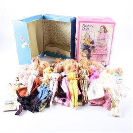 1970s and 1980s Barbie Assortment with Accessories: An assortment of 1970s and 1980s Barbies with accessories. This assortment features fourteen Barbie dolls and one Ken doll produced in the 1970s and 1980s by Mattel. The dolls wear a variety of Barbie and handmade clothing and include an assortment of loose clothing pieces with accessorizes such as shoes and purses. Also included are two storage trunks by Barbie and a vintage plastic doll.