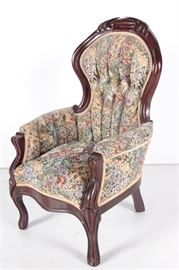 Upholstered Wooden Doll's Chair with Floral Pattern: An upholstered wooden chair with a floral pattern. This enclosed armchair features a curved headrest, scrolled arms with padding and cabriole legs. There is a materials tag to the underside of the seat.