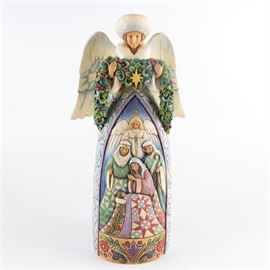 """Jim Shore """"Night Divine"""" Nativity Angel Statue: A resin statue by Jim Shore. Titled Night Divine this depicts a winged angel dressed in white winter furs holding an evergreen swag. There is a nativity scene in shallow relief in the front. It retains its original label underneath."""