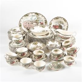 """Johnson Brothers """"Friendly Village"""" Tableware: An eighty five piece collection of Friendly Village tableware by Johnson Brothers England. This pattern was manufactured between 1958-2003 and depicts idyllic village scenes with foliate borders. Among the group are dinner plates, bowls, serving pieces and teacups. The pieces are marked to the base with the Johnson Brothers maker's mark."""