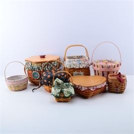 """Collection of Longaberger Handmade Holiday Baskets: A collection of handmade holiday themed baskets by Longaberger. This eight-piece assortment features a pink Picket Pale Easter basket with a pastel striped lining in pink, purple, yellow, blue, green, and white, a small square Sweetest Gift Valentines Day basket with a burgundy ribbon and heart pendant, a Sweetheart Love Letter heart-shaped basket with a white and red scroll pattern lining, and 2002 Mother's Day basket with a multicolored floral pattern lining with ruffles. These pieces are presented with a small square St. Patrick's Day basket with a green shamrock pattern lining, a round pink, green, yellow, and purple Easter basket with an Easter egg pattern lining, a round Little Pumpkin basket with a stem handle and a Jack O' Lantern pattern lining, and a hexagonal 1997 Snowflake Christmas basket with a holly berry and leaf pattern lining and a ceramic tag reading, """"Merry Christmas, 1997"""". These pieces are all marked, """"Longaberge"""