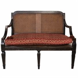 """Neoclassical Style Settee by Baker Furniture: A Neoclassical style cane settee by Baker Furniture. The bench features a black lacquered finish with gold tone detailing with vine and leaf accents to the front. It comes with a burgundy and gold tone removable cushion. It is marked """"Baker"""" to the underside."""