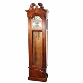 """Vintage Howard Miller Chiming Grandfather Clock: A vintage Howard Miller chiming grandfather clock. The clock features a silver and gold tone clock face with Arabic numerals and is marked """"Tempus Fugit"""" to the top. It has a broken arch style pediment to the top and fluted columns on the sides. It is marked """"Howard Miller Clock Co."""" to the top left panel. The model number is 610-232 and the serial number is 41590722."""