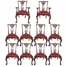 """Chippendale Style Dining Chairs: A set of ten Chippendale style dining chairs. The mahogany chairs have cabriole style legs with leaf accents to the legs and arms. There is an elegant carved back splat with scroll detailing to the top and sides. Each chair has a burgundy upholstery seat with gold tone polka-dots. The set includes two captain's chairs and eight side chairs. They are marked """"Furniture Land"""" to the underside."""