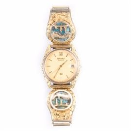 Seiko Wristwatch With 10K Yellow Gold, Opal and 22K Alaskan Gold Nugget Overlay: A Seiko wristwatch featuring 10K yellow gold bracelet attachments with genuine Alaskan 22K gold nuggets, and opal stone inlay, depicting a cabin with trees against the northern lights.
