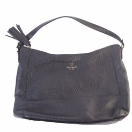Kate Spade Leather Handbag: A Kate Spade handbag in black leather with a gilt brand marking to the top edge of the face. The bag has a single strap and a zippered top with a tassel pull. The inside is lined with a black and white striped textile. A brand patch and serial number label are present to the interior.