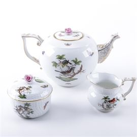 "Herend ""Rothschild Bird"" Tea Set: A three-piece tea set in the Rothschild Bird pattern by Herend. It comes with a teapot, a creamer, and a lidded sugar bowl. The teapot and the sugar bowl feature rose finials. The sugar bowl contains a hammered body. All feature bird and branch hand-painted print designs. Items contain gilding as well and are stamped to the undersides."
