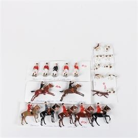 W. Britain Cast Toy Huntsman Figures: A collection of W. Britain cast toy huntsman figurines. This collection features twenty-two figurines comprised of cast metal produced by W. Britain. The toy figurines are presented in British Huntsman garb with hand painted detailing. Figurines include horse riders, hunting dogs, and figures resting on green bases.