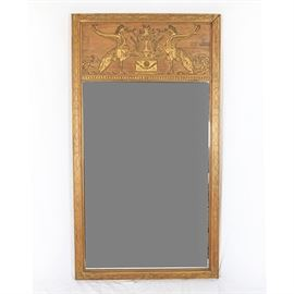 Hand-Carved Wooden Wall Mirror By Palladio: A hand-carved wooden wall mirror by Palladio. This rectangular mirror is housed in a partially gilded frame. It features a horizontal panel above the mirror, the panel depicting two griffins, mythical creatures that are part eagle and part lion. The griffons face one another, with a large pedestal and Romanesque vessel between them. A hanging wire is included. The mirror is marked on the reverse.