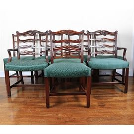 Set of Vintage Chippendale Style Mahogany Dining Chairs: A collection of eight vintage Chippendale style dining chairs. This set includes chairs with mahogany frames and green upholstered seat cushions. Two of the chairs feature armrests rising on curved supports. The chairs feature a curved crest rail with pierced and scrolling ladderback and rising on straight legs joined by an H-stretcher. There are no visible maker's marks.