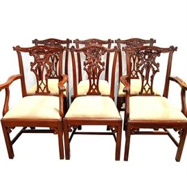 Chippendale Style Mahogany Dining Chairs: A group of six Chippendale style mahogany dining chairs. The group includes two armchairs and four side chairs. Each has an arched crest with scrolled ears above a pierced and carved splat and a padded, slip seat. The seat is covered in beige, dot-patterned fabric and the chairs rise on Marlborough legs with scrolled returns joined by H-stretchers.