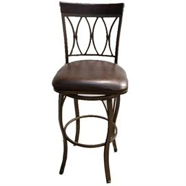 Metal Chair-Back Bar Stool: A metal chair-back bar stool. The frame features a curved, wooden crest in a dark stain above a pierced back with incurvate, metal splats. The padded seat is covered in brown vinyl upholstery and the bar stool rises on cabriole legs joined by a circular stretcher. There are no visible maker's marks.