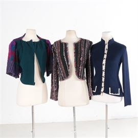 Women's Vintage Jackets Including St. John: An assortment of women's vintage jackets. This collection includes a navy blue knit sweater by St. John Knits for Palais Royal with a mock neck and button-down front; a black and pink knit sweater with an open front by Sandi Wright of Sante Fe, New Mexico and a green and plaid B. Artise Originals sweater with an open front and knit back.