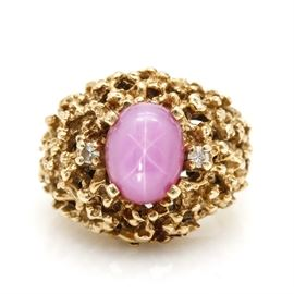 14K Yellow Gold Pink Star Sapphire and Diamond Ring: A 14K yellow gold synthetic pink star sapphire and diamond ring. This ring features a center oval synthetic pink star sapphire flanked by two diamonds within an openwork textured dome setting.