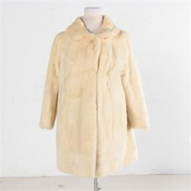 Women's Vintage Platinum Mink Coat: A women's vintage circa 1960s platinum mink coat by The Bon Marche. This mid length coat features a rounded collar, hook and eye closures along the front, full length sleeves, slash pockets and a white satin lining marked with a cloth label and an embroidered personalization.