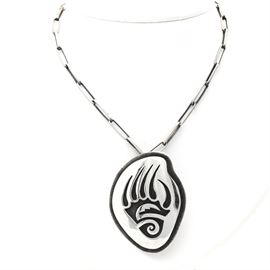 Joe Josytewa Hopi Overlay Bear Paw Converter Pendant Necklace: A handcrafted sterling silver bear paw overlay converter pendant or brooch and chain by Hopi silversmith, Joe Josytewa. This piece features an overlaid silver bear paw motif with a textured, oxidized background. The converter adorns a handcrafted cable link chain.
