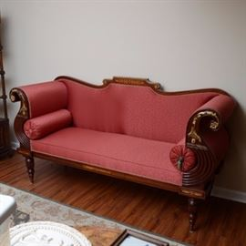 Closson's Empire Style Sofa: A Closson's empire style sofa. This sofa is set on a wooden base and upholstered in a red vine pattern. The sofa features curved armrests fitted with cylindrical pillows with tassels on either end. The wooden frame features reeded details and a carved floral design. Some of these carved floral designs are painted in a gold-tone paint. The legs of this sofa are tapered. Located in lower level of home with access to garage.