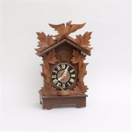 German Made Cuckoo Clock: A cuckoo clock made in West Germany. This fine hand crafted clock is desgined with a bird in flight to top with leaves to either side which follows down the sides. A black face with white Roman numeral hour markers and pierced hands. A little bird will appear from behind closed door. Key is present.