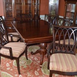Dining Table and Eight Chairs: A dining table with eight armchairs. The wood table features a tabletop with veneer inlay in a diamond pattern and two large turned pedestal bases, each with four spider legs. The tabletop can be extended with the addition of two 15 inch leaves. It is accompanied by eight armchairs with arched back with openwork design of intersecting ovals. The armchairs include seats upholstered in a brick red and tan stripe fabric, which stand on square, tapered legs. The group is located on first level of home.