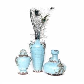 Grouping of Clay Pottery Vases: A grouping of clay pottery vases. These three vases include a tall slender neck vase with authentic peacock feathers, a small covered urn vase and a water vessel. All are decorated with grapes and leaves to sides and painted in a sky blue.
