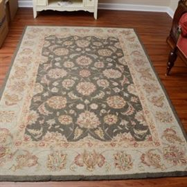 Hand Hooked Davenport Collection Area Rug: A hand hooked wool area rug. This Davenport Collection rug is in green shades with warm beige floral designs and border. It has bound seams to the underside and a full backing. It was made in China and is tagged to the underside.